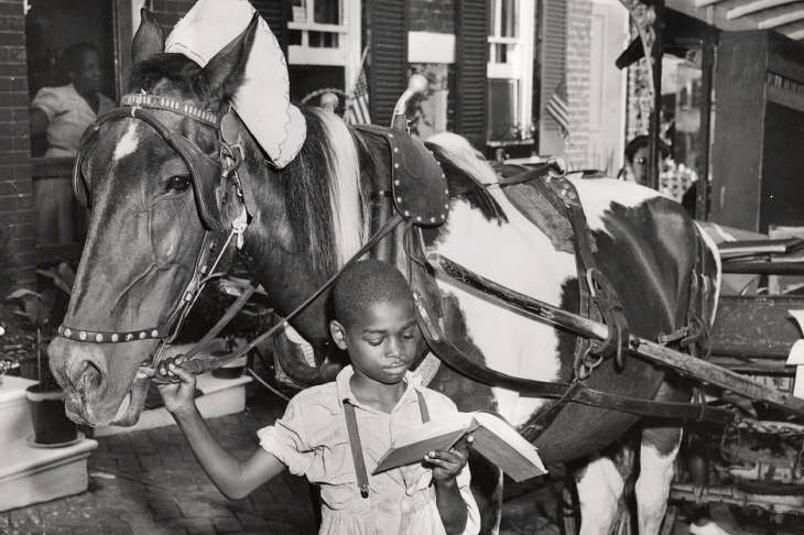 Pratt Library Book Wagon - historic photo of a boy reading a library book while holding the horse's bridle