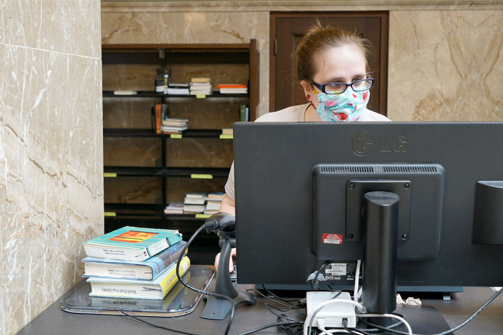 Library staff checking out books with a mask on during COVID-19
