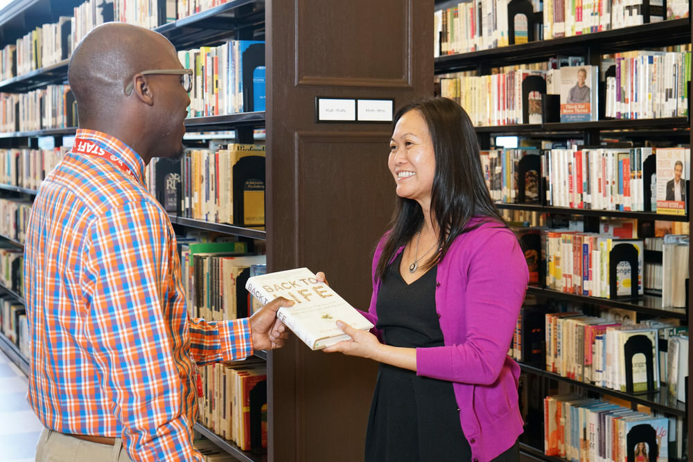 Pratt staff handing a customer a book