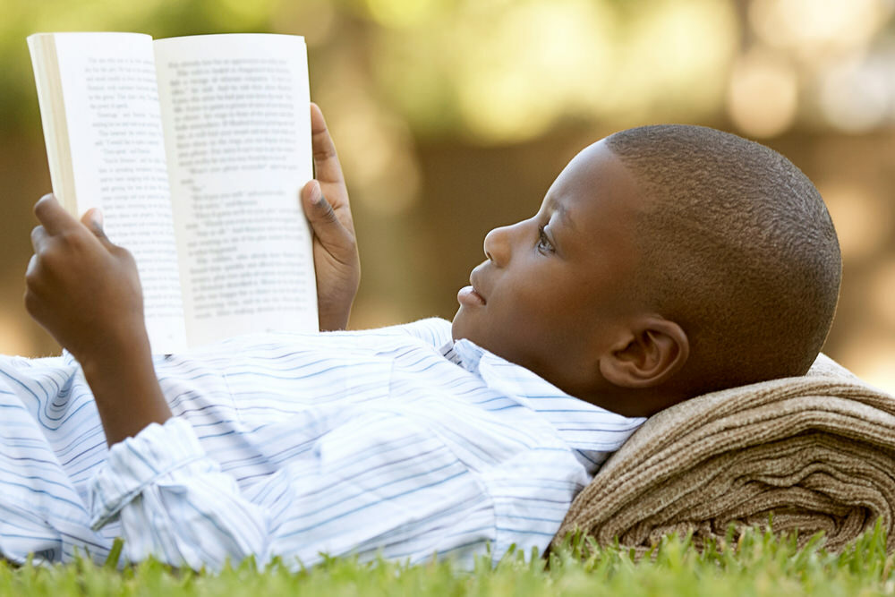 boy reading a book outside in summer