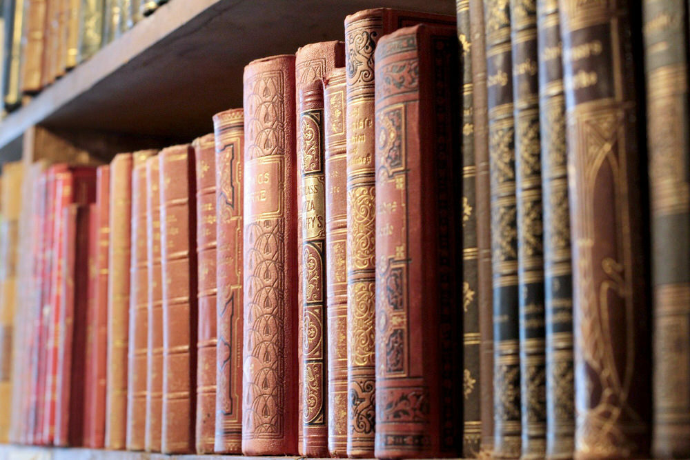 old books on a shelf with gold embossed leather spines