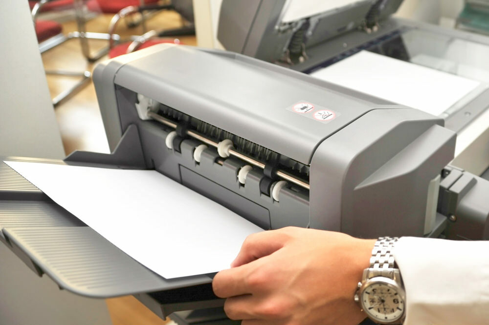 printer or copier - hand reaching for paper