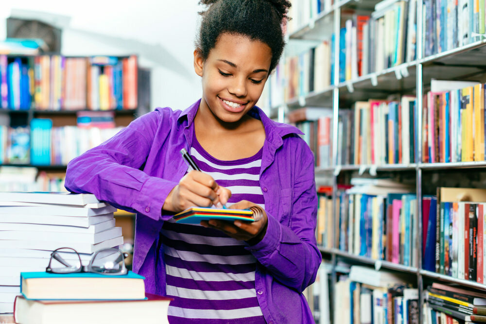 teen girl surrounded by books, writing in a notepad