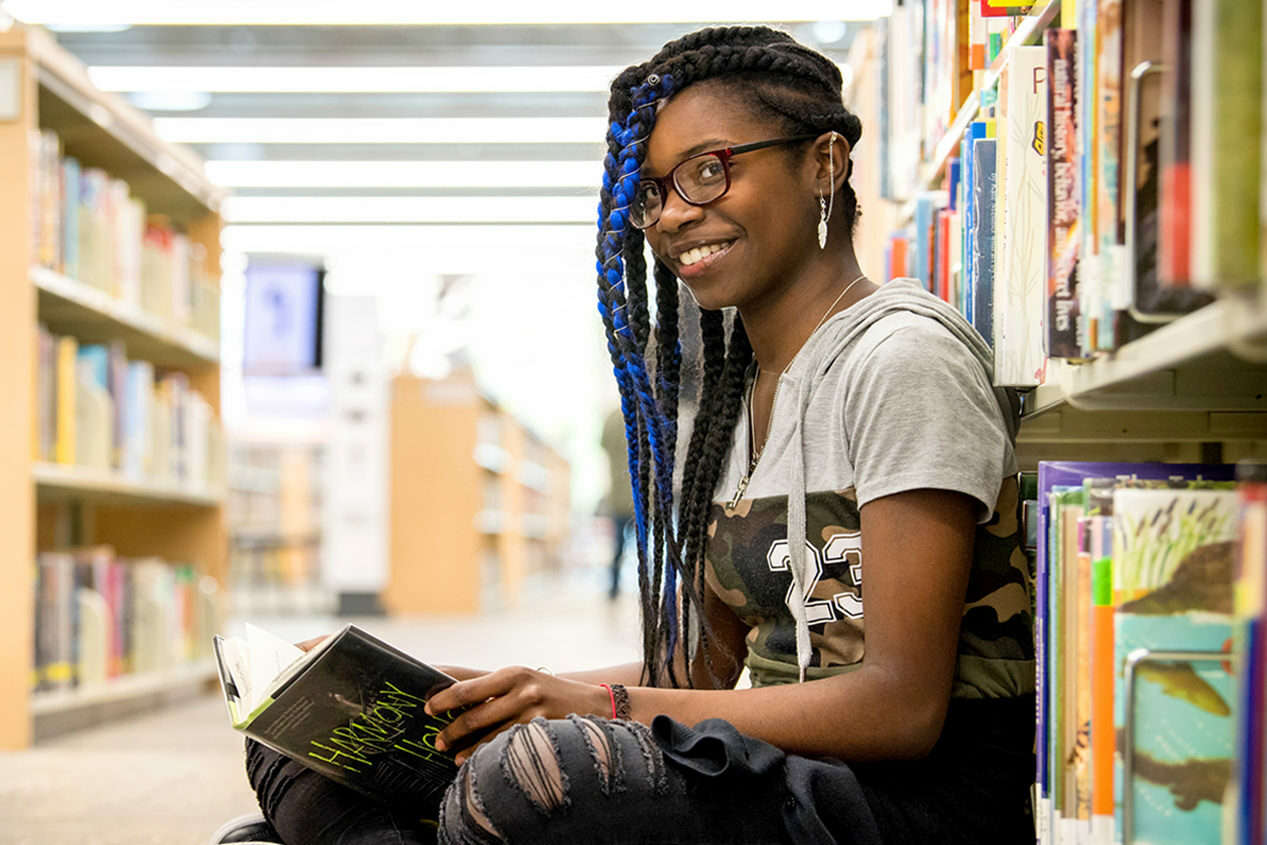 teen girl smiling, sitting on the floor with a book at the library