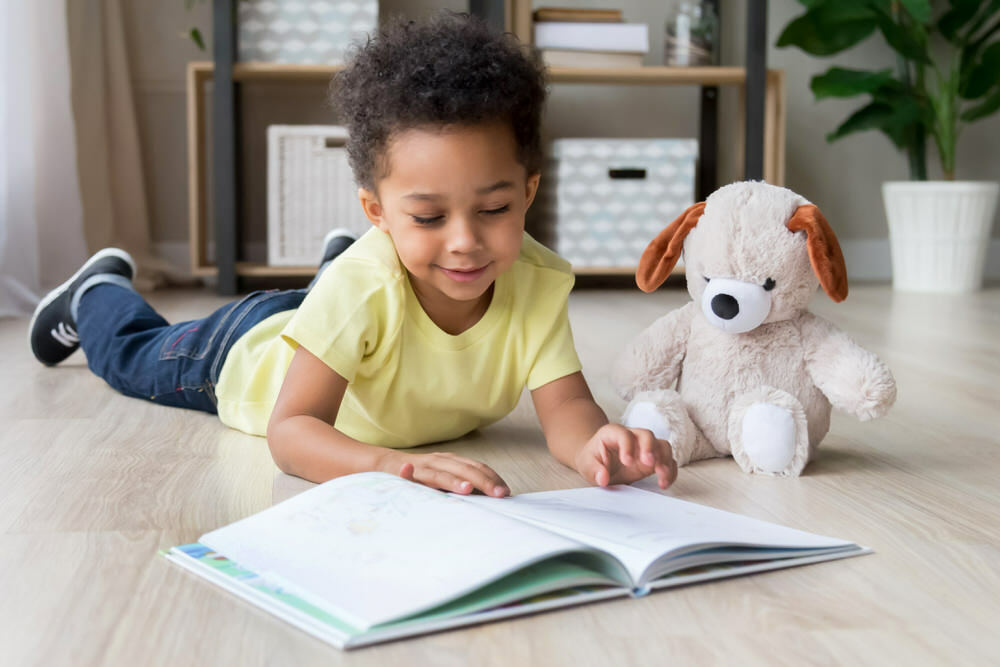 Toddler reading book on the floor with teddy bear