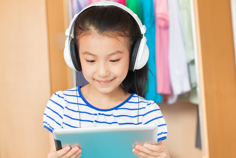 young girl with headphones and tablet at home