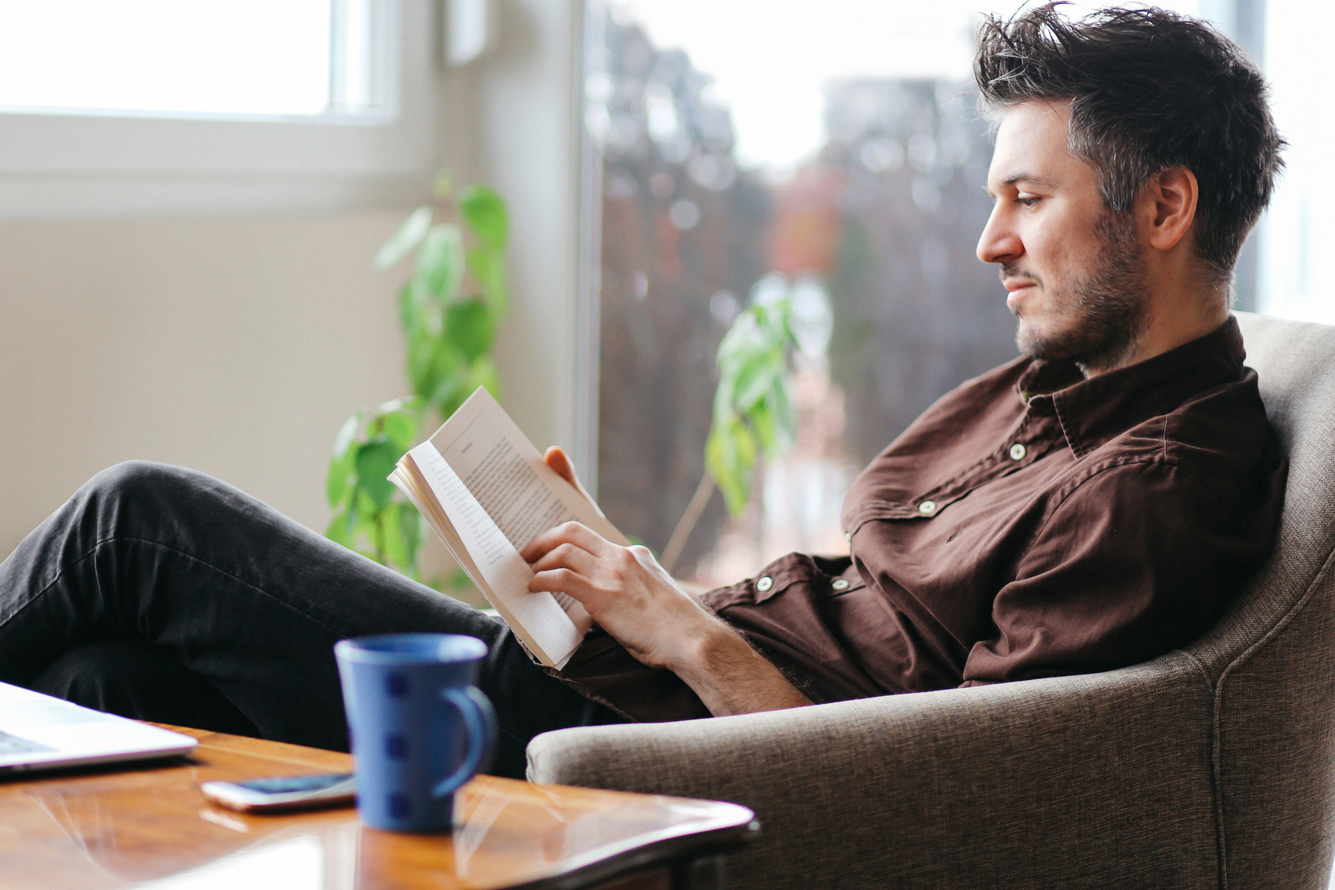 man reading at home with coffee and laptop