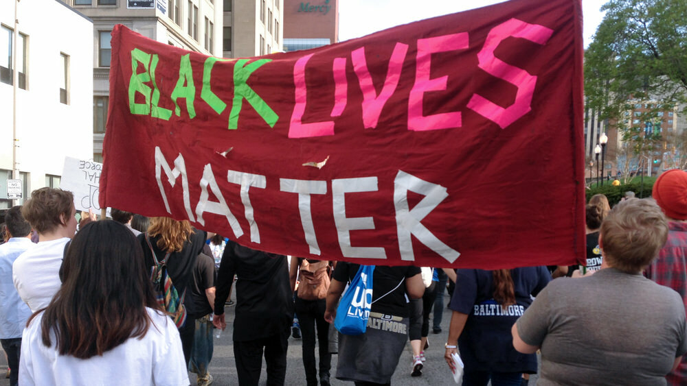 people in Baltimore marching and holding a protest sign reading Black LIves Matter, from surgebaltimore.org