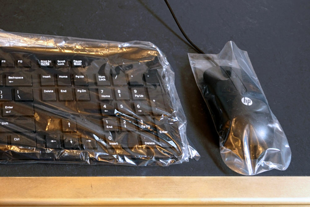 computer keyboard and mouse under plastic for safety