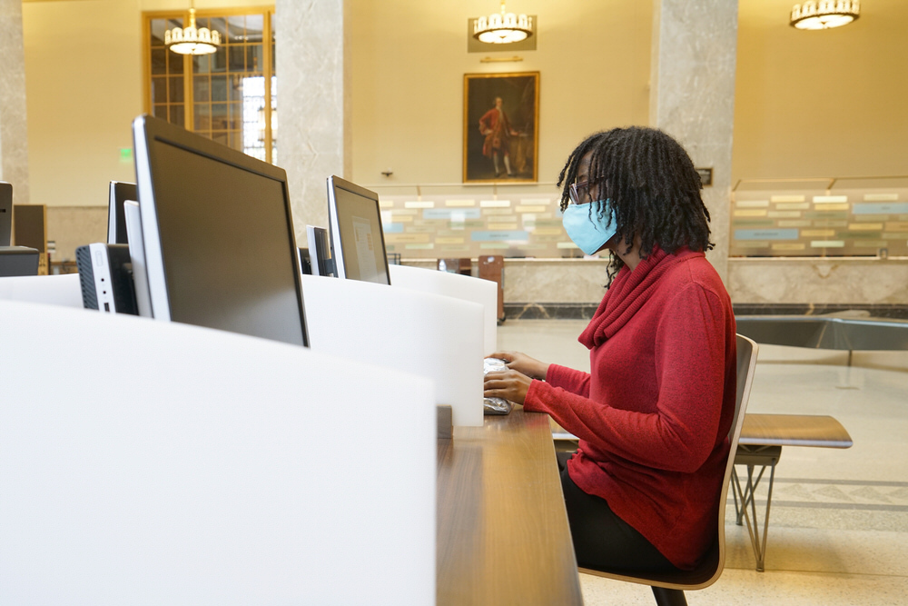 customer using public library computers with a face covering for safety