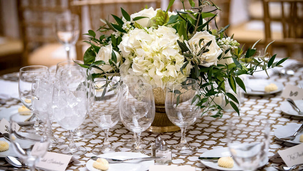 event table set with flowers, glasses, place settings