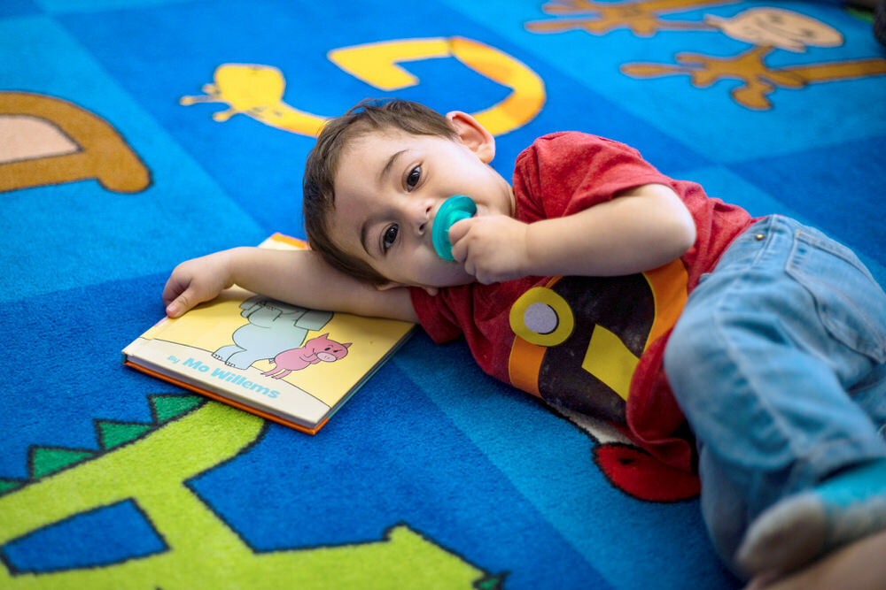 young boy with pacifier with book on rug at Patterson Park storytime